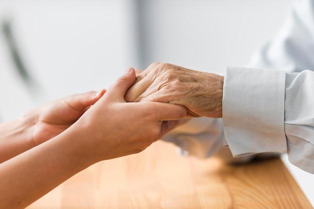Enfermeira segurando as mãos de um homem sênior para se sentir confortável Foto gratuita