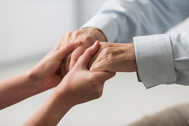 Enfermeira segurando as mãos de um homem sênior por simpatia Foto gratuita