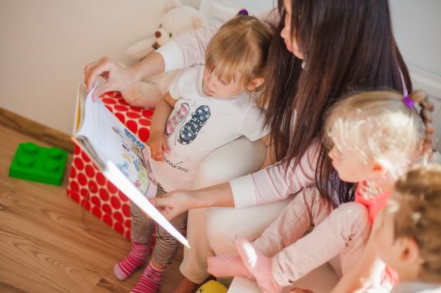 Enfermeira sentada com crianças e livro de leitura Foto gratuita