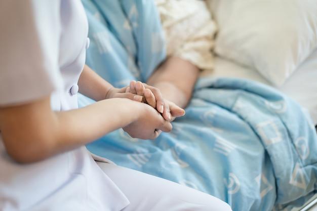 Enfermeira, sentando, ligado, um, cama hospital ao lado, um, mulher mais velha, ajudando, mãos, cuidado, para, a, idoso, conceito Foto Premium