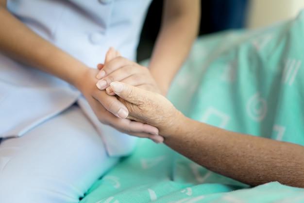 Enfermeira, sentando, ligado, um, cama hospital ao lado, um, mulher mais velha, ajudando, mãos Foto Premium
