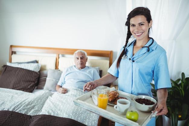 Enfermeira servindo café da manhã para homem sênior Foto Premium