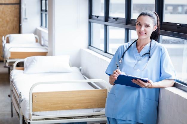 Enfermeira, sorrindo para a câmera na ala do hospital Foto Premium