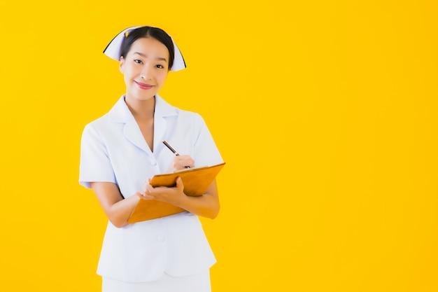 Enfermeira tailandesa de bela jovem mulher asiática retrato com quadro branco vazio Foto gratuita