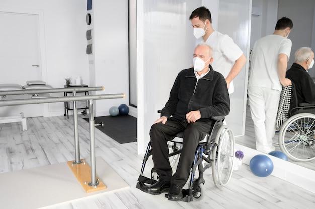 Enfermeiro atendendo paciente idoso com deficiência em cadeira de rodas em centro de reabilitação. Foto Premium