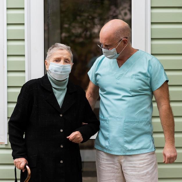 Enfermeiro e mulher sênior com bengala em casa de repouso Foto gratuita