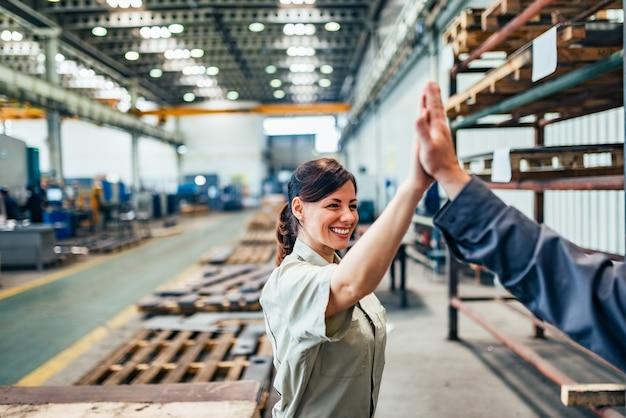 Engenheira de alta cinco com o colega no hall de fábrica. Foto Premium