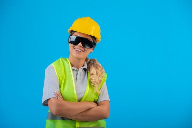 Engenheira em capacete amarelo e equipamento usando óculos preventivos de raio se passando por um profissional. Foto gratuita