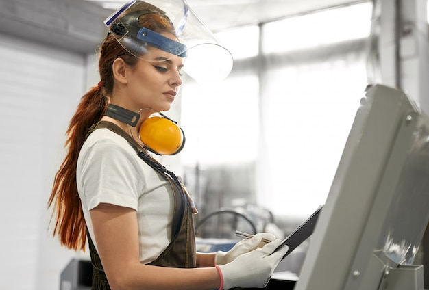Engenheira em roupas de proteção trabalhando na fábrica. Foto gratuita