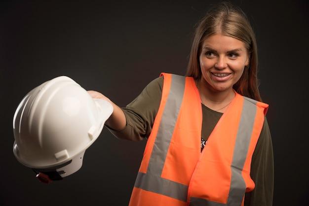 Engenheira segurando um capacete branco e parece positiva. Foto gratuita