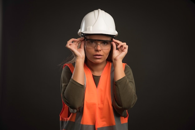 Engenheira usando um capacete branco, óculos e equipamento. Foto gratuita
