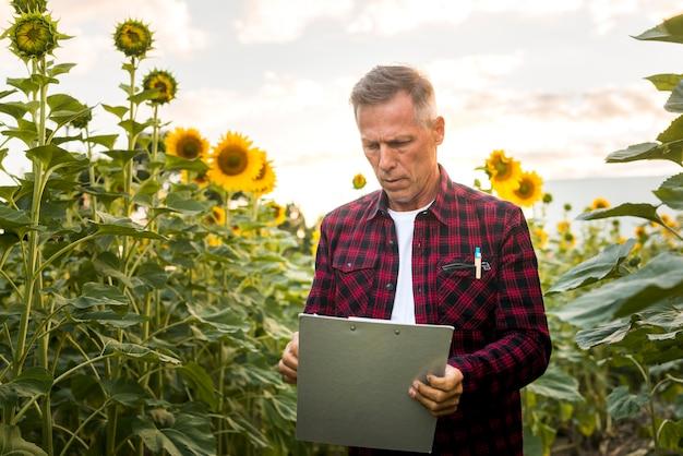Engenheiro agrônomo olhando atentamente para uma prancheta Foto gratuita