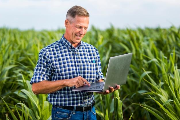 Engenheiro agrônomo sorridente usando um laptop Foto gratuita
