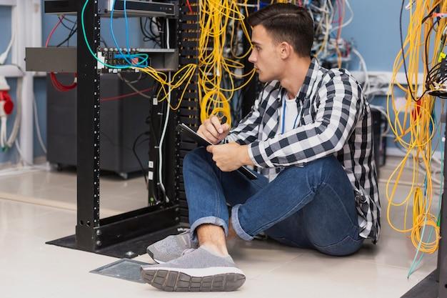 Engenheiro bonito trabalhando na sala do servidor Foto gratuita