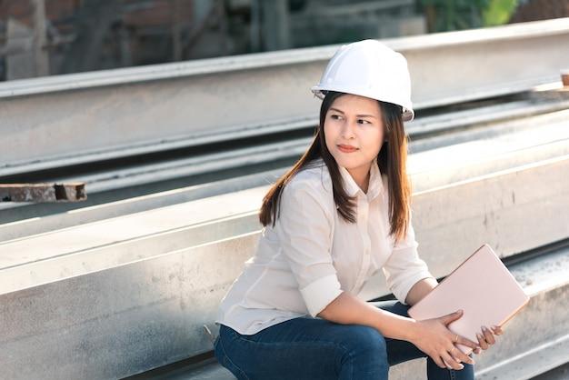 Engenheiro civil da mulher asiática com o canteiro de obras branco da visita do capacete de segurança. Foto Premium