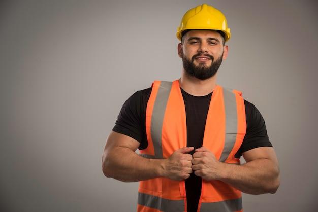 Engenheiro com uniforme laranja e capacete amarelo parece confiante Foto gratuita