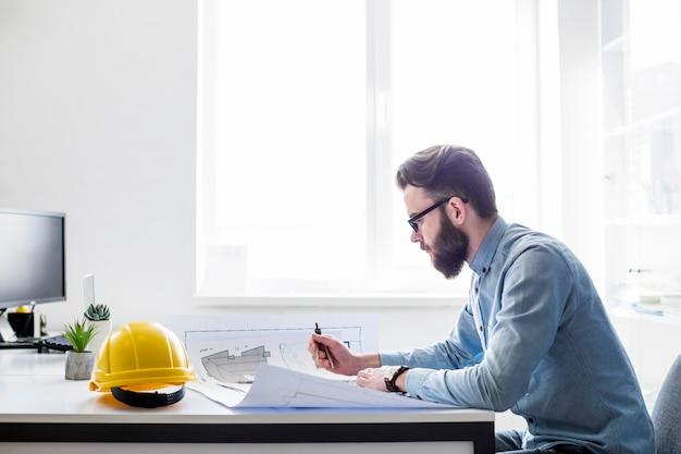 Engenheiro criativo trabalhando na planta de construção no local de trabalho Foto gratuita
