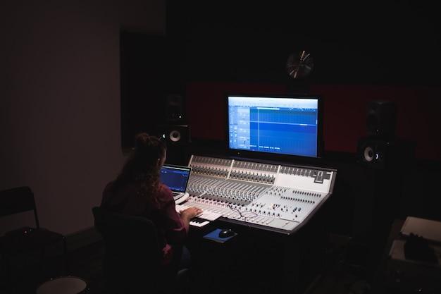 Engenheiro de áudio masculino usando mixer de som Foto gratuita
