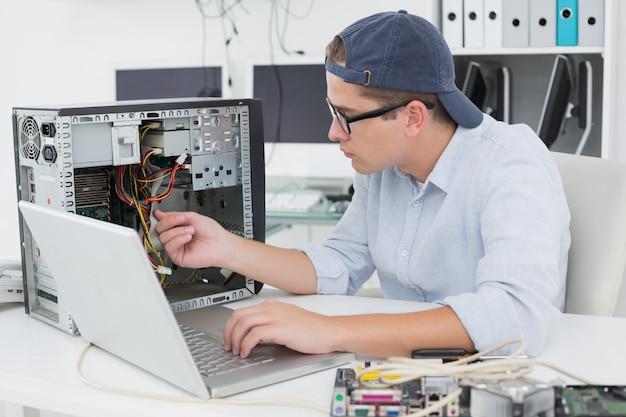 Engenheiro de computação trabalhando no console quebrado com laptop Foto Premium