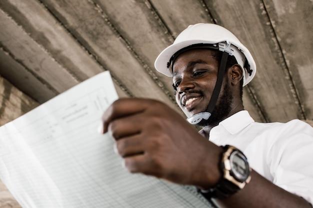 Engenheiro de construção africano olhando plantas enquanto usava capacete Foto Premium