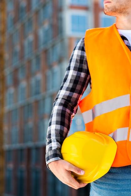 Engenheiro de construção de close-up segurando o capacete Foto gratuita