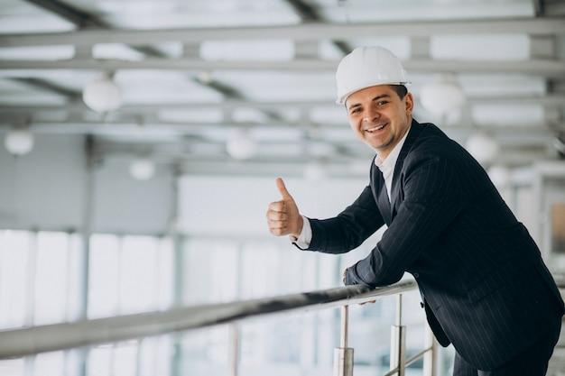 Engenheiro de homem de negócios bonito no capacete em um edifício Foto gratuita