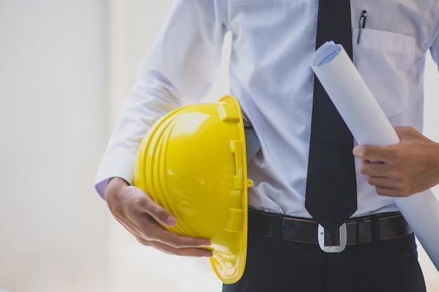 Engenheiro de homem segurando capacete capacete trabalho construção construção Foto Premium