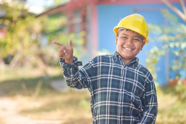 Engenheiro de menino construção preencher sorriso feliz diversão em ação Foto Premium