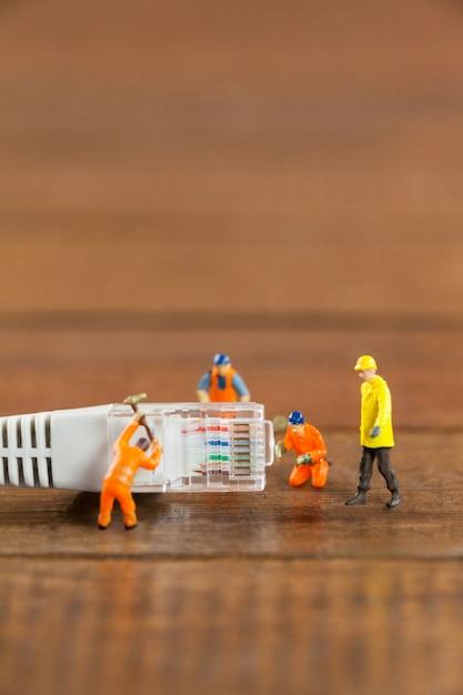 Engenheiro de miniatura e trabalhadores que trabalham com cabo lan Foto gratuita