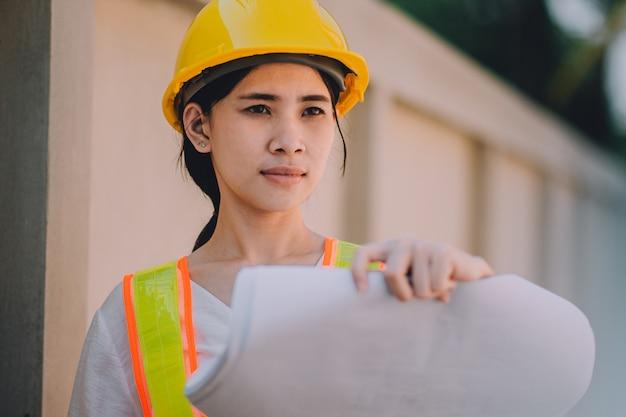 Engenheiro de mulheres asiáticas segurando o canteiro de obras de trabalho Foto Premium