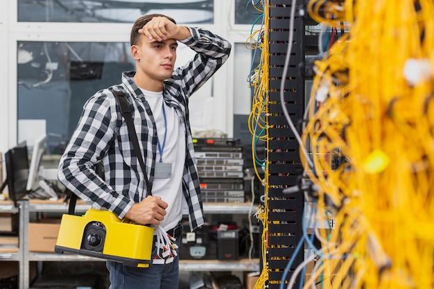 Engenheiro de rede cansado com uma caixa trabalhando em switches ethernet Foto gratuita