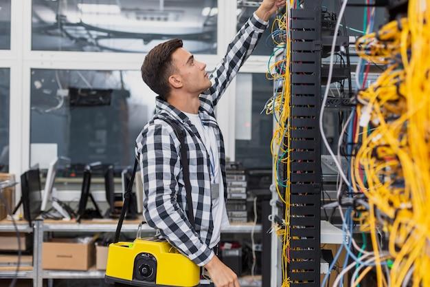 Engenheiro de rede jovem com uma caixa olhando para switches ethernet Foto gratuita