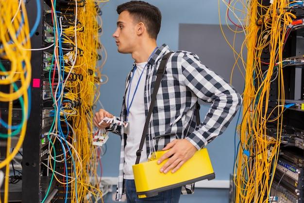 Engenheiro de rede jovem olhando para switches ethernet Foto gratuita