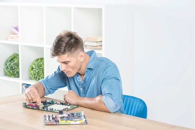 Engenheiro de ti masculino praticando para reparar a placa-mãe Foto gratuita