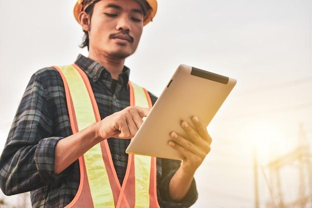 Engenheiro eletricista usa um tablet para inspecionar a rede da usina para geração de energia Foto Premium