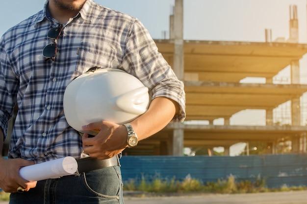 Engenheiro em profissional segurando um capacete de pé no canteiro de obras da frente. Foto Premium