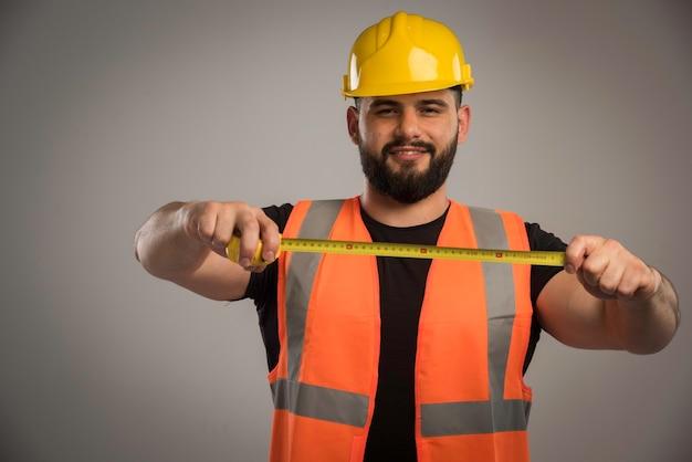 Engenheiro em uniforme laranja e capacete amarelo usando régua Foto gratuita