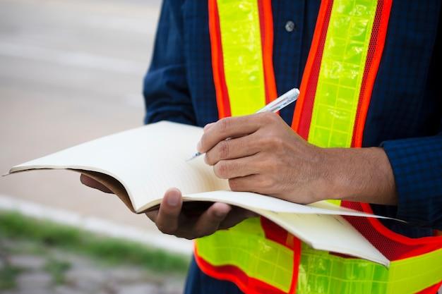 Engenheiro escrever tomar nota no livro para aplainar o trabalho Foto Premium
