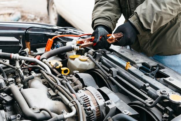 Engenheiro mecânico carregando bateria de carro com eletricidade usando cabos jumper ao ar livre Foto Premium