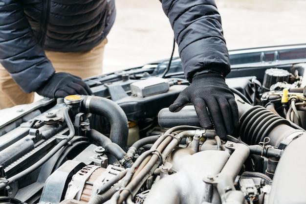 Engenheiro mecânico de automóveis, consertando o carro, tornando a manutenção abrangente da verificação automática. mecânico de automóveis em luvas detectou avaria no serviço de reparo do carro. Foto Premium