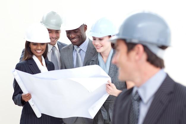 Engenheiro olhando para a equipe estudando um plano Foto Premium