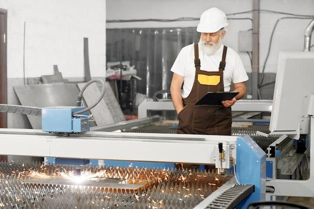 Engenheiro profissional que controla o processo de corte a plasma Foto gratuita
