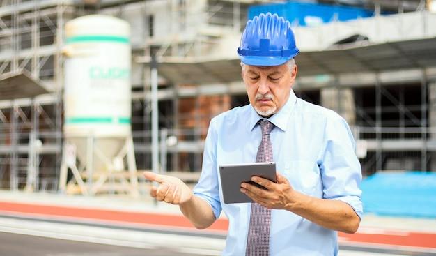 Engenheiro sênior homem de terno e capacete trabalhando no tablet pc em uma expressão de céticos Foto Premium
