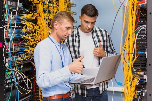 Engenheiros de rede jovens com um laptop tiro médio Foto gratuita