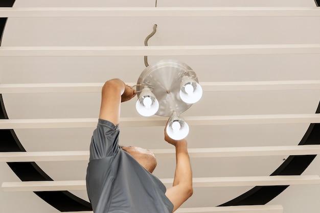Engenheiros elétricos estão instalando lâmpadas de teto no corredor. Foto Premium