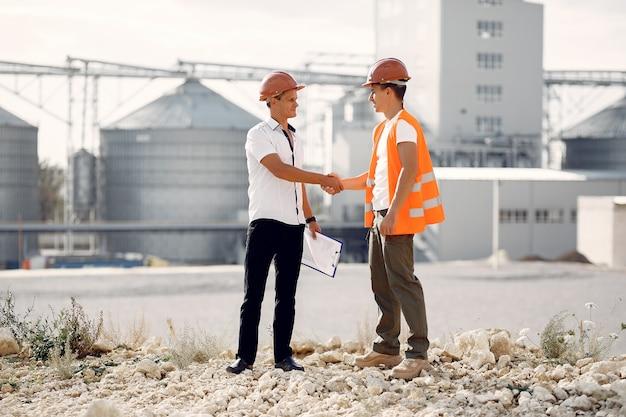 Engenheiros em capacetes de pé pela fábrica Foto gratuita