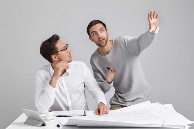 Engenheiros entusiasmados trabalham juntos no projeto de construção, gesticulando para apresentar seus planos e ideias futuras Foto gratuita