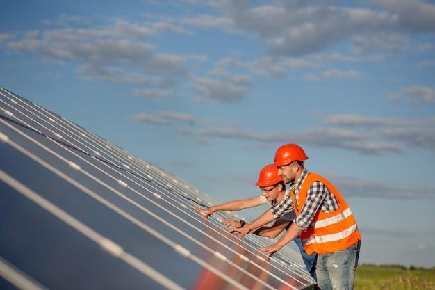 Engenheiros mantendo painéis solares no campo. Foto Premium