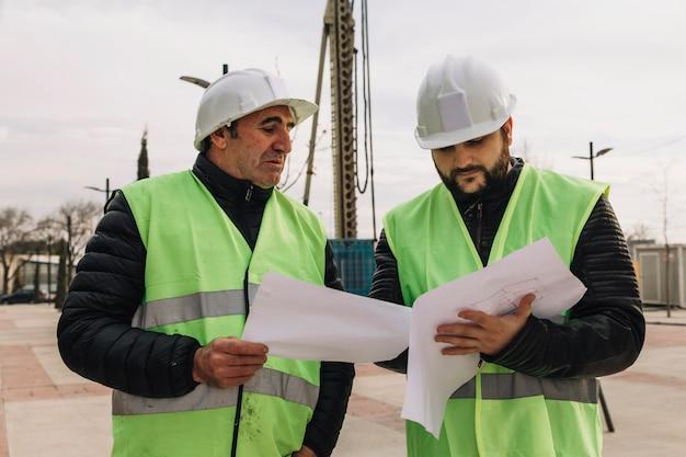 Engenheiros olhando rascunhos no canteiro de obras Foto gratuita