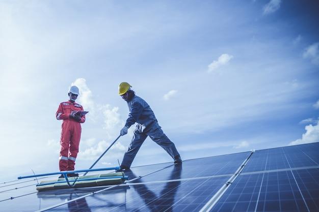 Engenheiros que operam e verificar a geração de energia da usina de energia solar no telhado solar Foto Premium